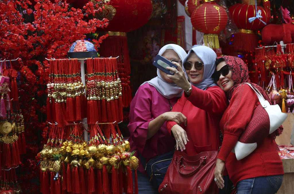 In this Monday, Jan. 28, 2019, photo, Muslim women take a selfie at a shop selling Lunar New Year decorations in the Chinatown area of Jakarta, Indone