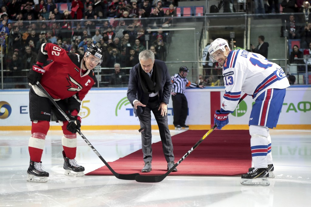 Former Manchester United coach Jose Mourinho, center, makes the first puck drop at Monday's Kontinental Hockey League game between Avangard Omsk and S...