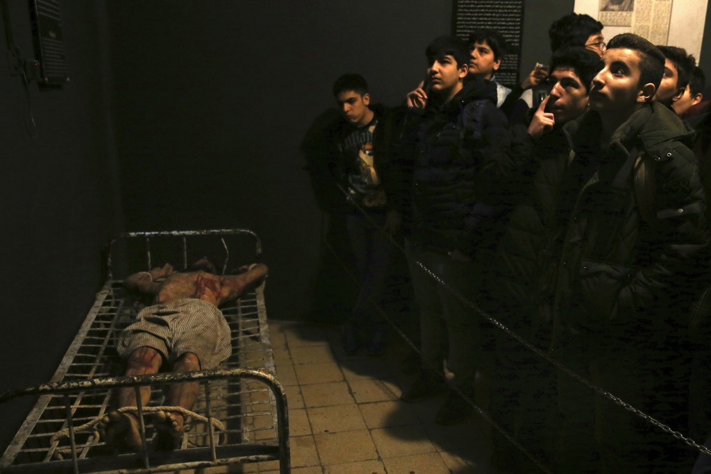 In this Jan. 7, 2019 photo, Iranian schoolboys look at an exhibition at a former prison run by the pre-revolution intelligence service, SAVAK, now a m