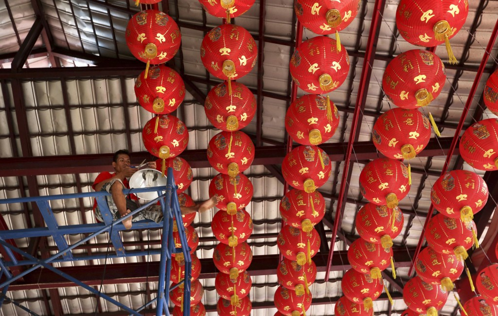In this Jan. 29, 2019, photo, a worker sits high up in the eves to arrange lanterns in preparation of the Lunar New Year at a temple in Jakarta, Indon