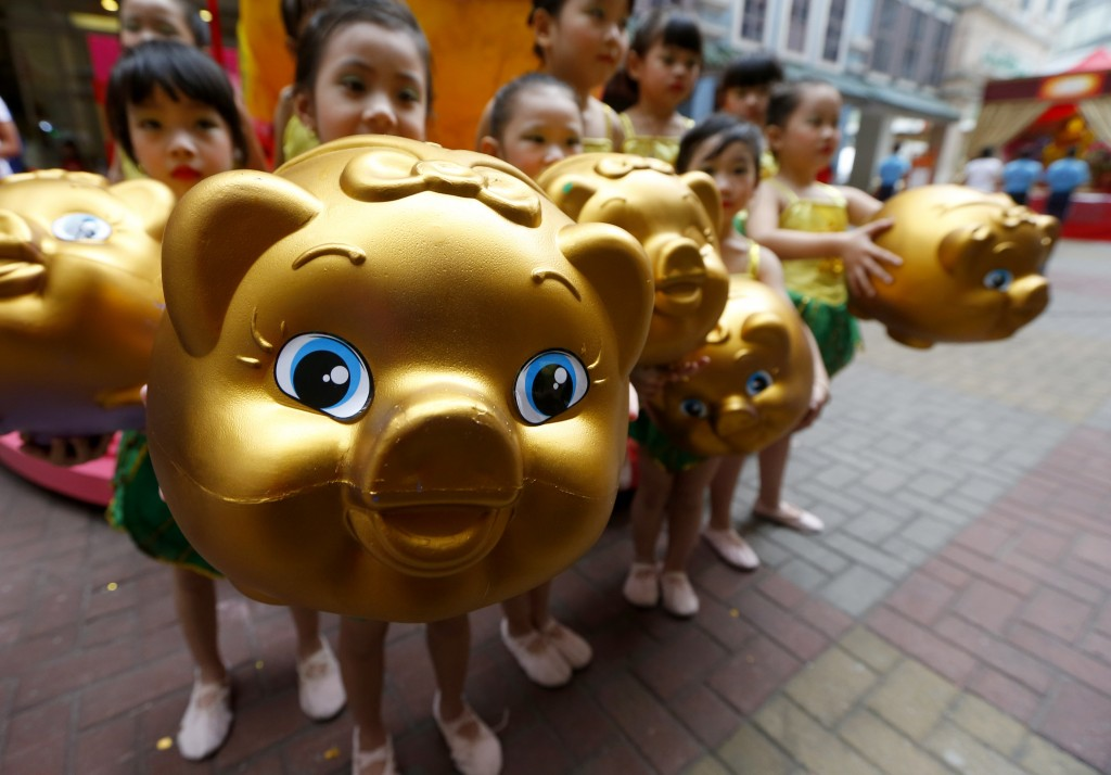 In this Friday, Feb. 1, 2019, photo, Filipino-Chinese display piggy banks at the start of celebrations leading to next week's Lunar New Year in Chinat