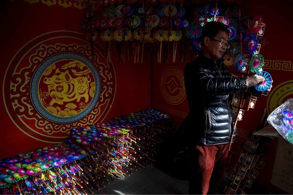 In this Sunday., Feb. 3, 2019, photo, a vendor adds a wooden windmill toy to his store at the Longtan Park for a temple fair ahead of Chinese Lunar Ne