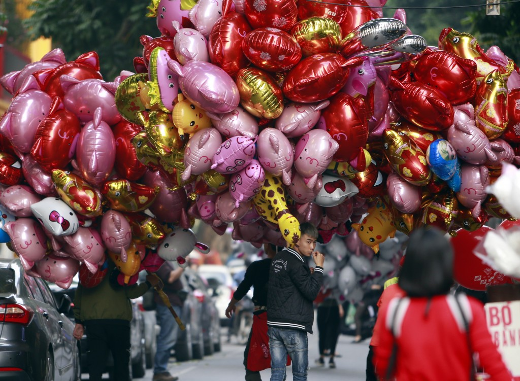 In this Sunday, Feb. 3, 2019, photo, vendors carrying pig-shaped balloons for sale to mark the Lunar New Year in Hanoi, Vietnam. Vietnam is celebratin