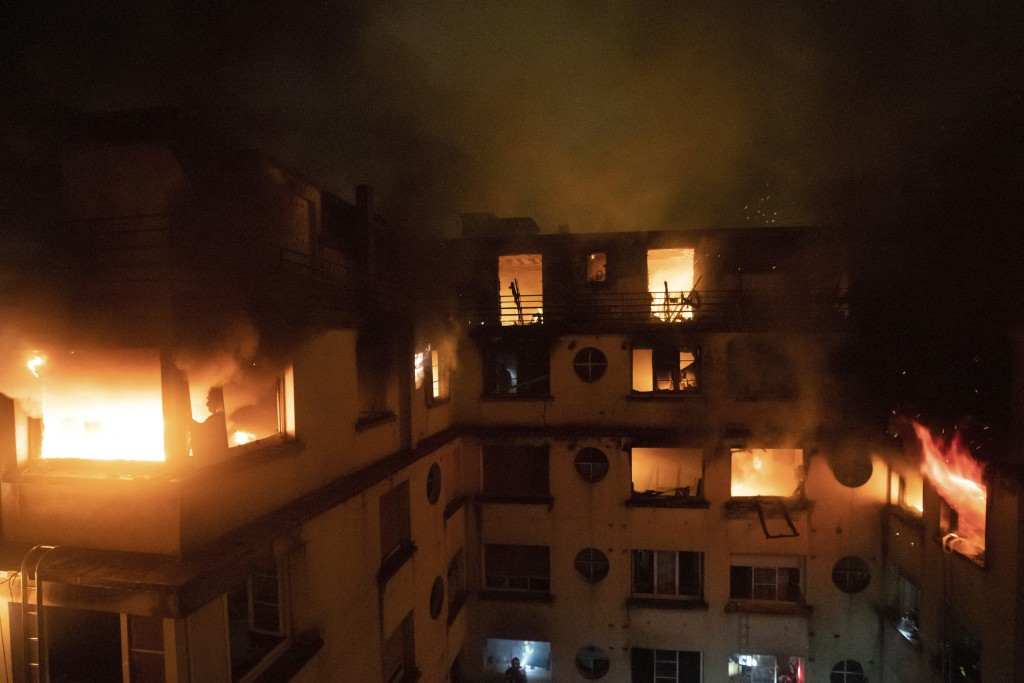 In this photo provided on Tuesday, Feb. 5, 2012 by the Brigade de Sapeurs-Pompiers de Paris (Paris Fire Brigade), a fire rages through the top floors ...