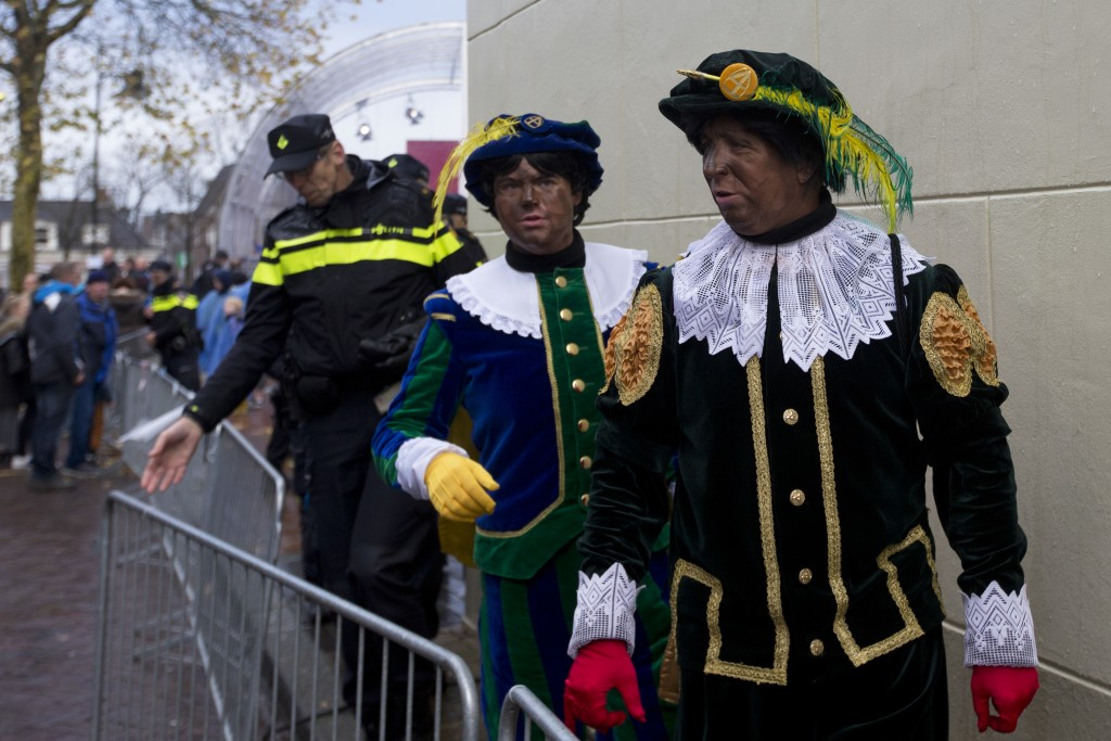FILE - In this Nov. 18, 2017, file photo, Black Petes and police officers leave after the arrival of Sinterklaas, or Saint Nicholas in Dokkum, norther