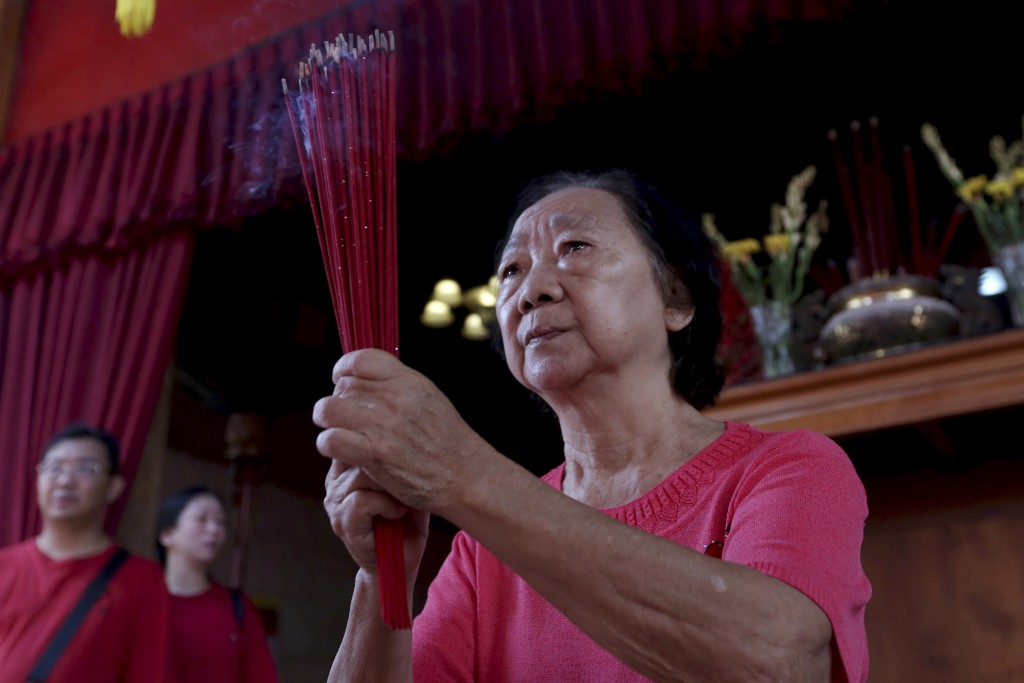 An Indonesian ethnic Chinese woman holds incense sticks as she pray during the celebration of the Lunar New Year at a temple on the outskirts of Jakar