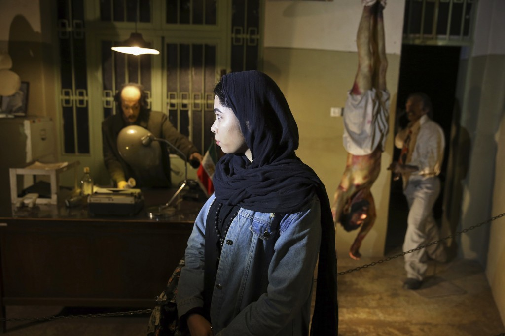 In this Jan. 7, 2019 photo, an Iranian looks at an exhibition at a former prison run by the pre-revolution intelligence service, Savak, now a museum,