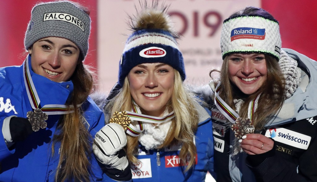 United States' Mikaela Shiffrin, center, shows her gold medal of the women's super-G, flanked by silver medallist Italy's Sofia Goggia, left, and bron...