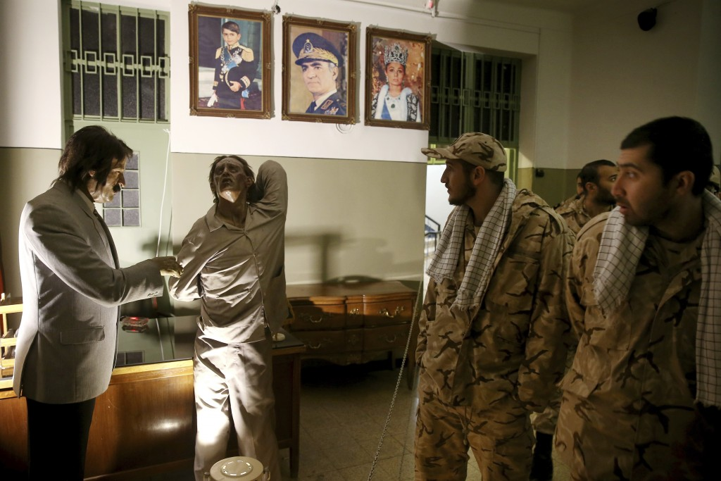 In this Monday, Jan. 7, 2019, photo, Iranian Revolutionary Guard soldiers look at an exhibition at a former prison run by the pre-revolution intellige