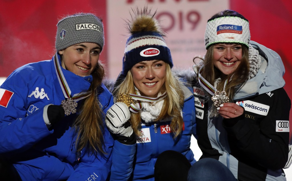 United States' Mikaela Shiffrin, center, shows her gold medal of the women's super-G, flanked by silver medallist Italy's Sofia Goggia, left, and bron
