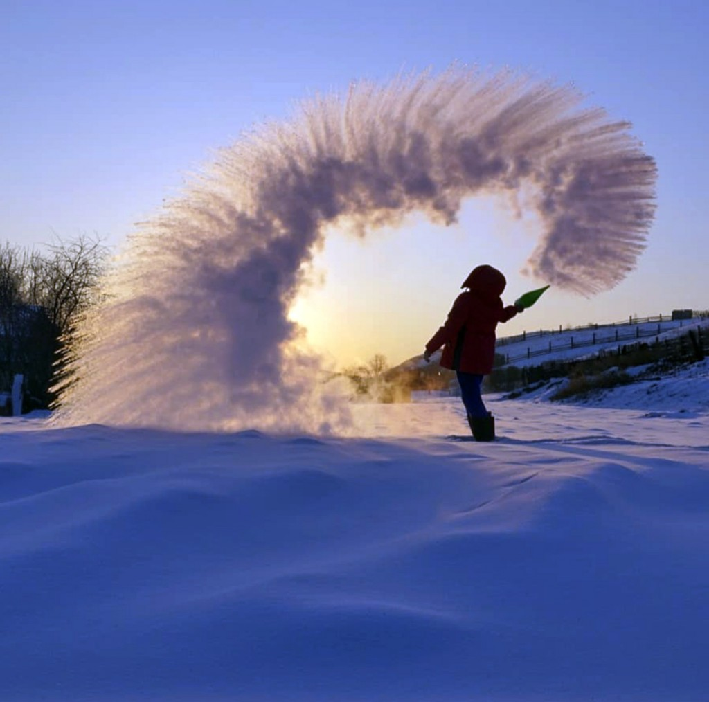 In this handout photo taken on Tuesday, Feb. 5, 2019, a woman throws boiling water into the freezing air as its instantly condenses into an elaborate