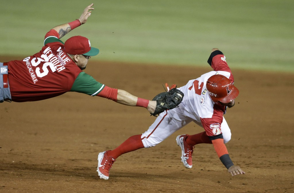In this Feb. 4, 2019 photo, Alexi Amarista of Venezuela's Cardenales de Lara, right, is tagged out at first by Victor Mendoza of Mexico's Los Charros ...