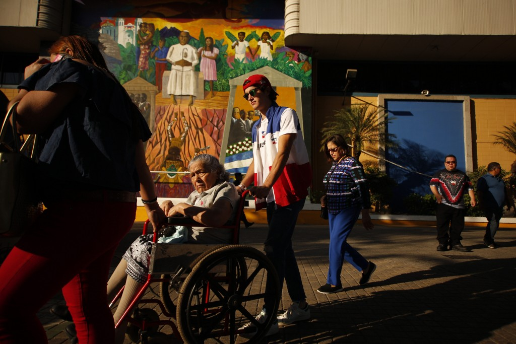 In this Feb. 3, 2019 photo, an election volunteer helps a woman in a wheelchair reach her voting table during the presidential election in San Salvado