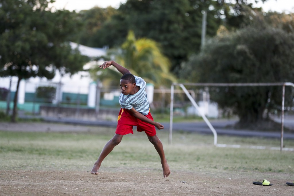 In this Feb. 3, 2019, photo, Jewel Andrew plays cricket at a school yard in St. John's , Antigua and Barbuda, the day after West Indies defeated Engla...