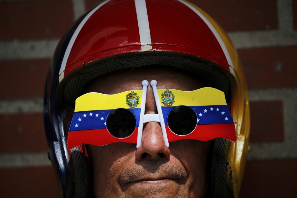 In this Feb. 2, 2019 photo, an anti-government protester wears Venezuelan flag motif sunglasses during a demonstration demanding the resignation of Pr