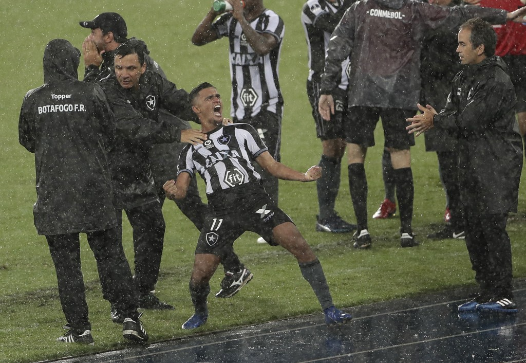 In this Feb. 6, 2019 photo, Erik of Brazil's Botafogo celebrates scoring his side's first goal during a Copa Sudamericana soccer match in the rain aga...