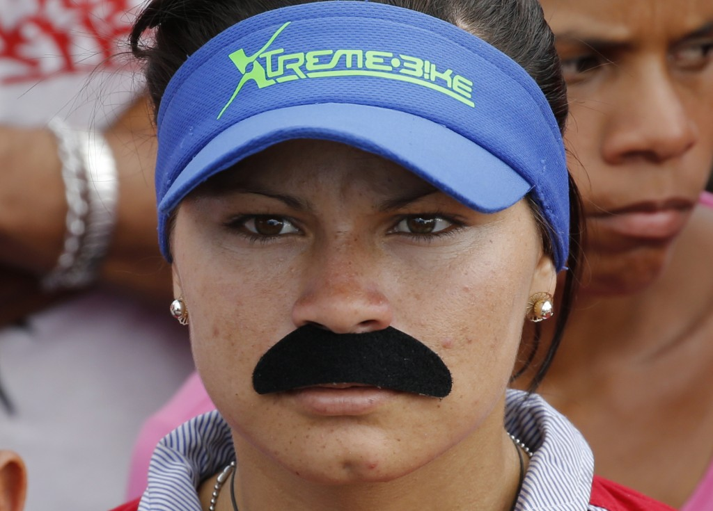 In this Feb. 2, 2019 photo, a woman dons a fake mustache emulating that of Venezuela's Nicolas Maduro, at a pro-government rally in Caracas, Venezuela