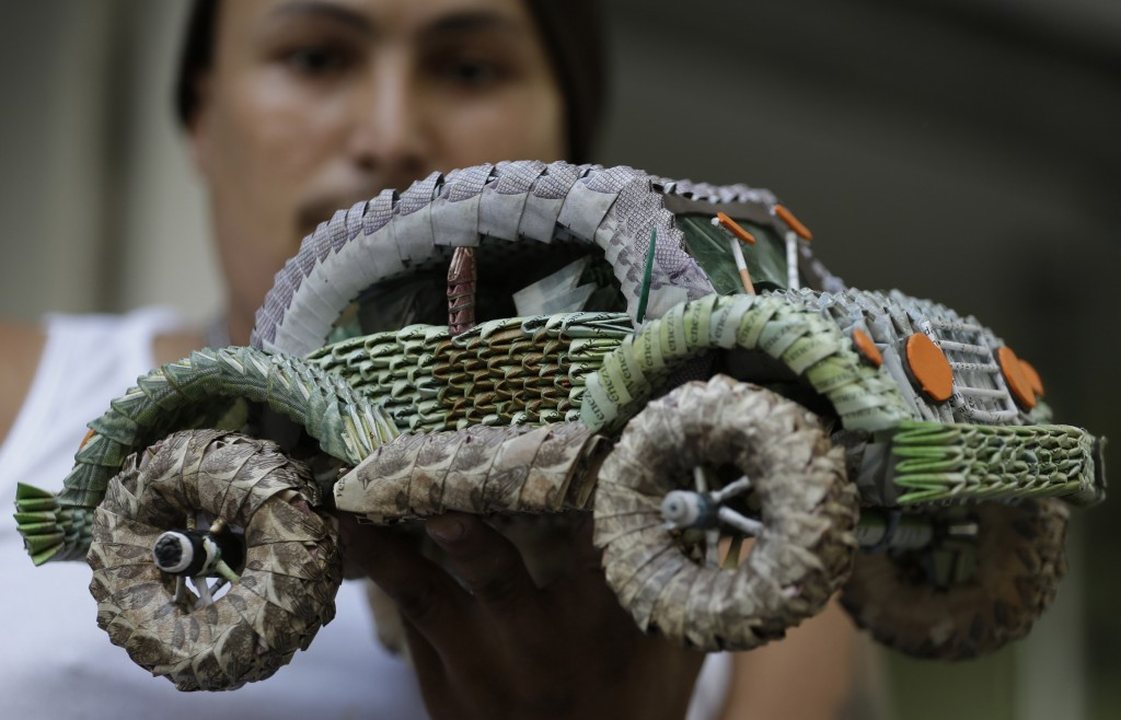 In this Feb. 6, 2019 photo, Venezuelan migrant Edixon Infante shows a handicraft made in with devalued Venezuelan currency, in Cucuta, Colombia. The V...