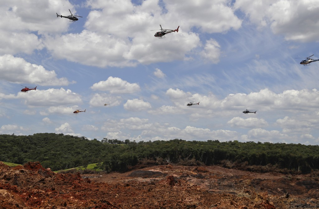 In this Feb. 1, 2019 photo, helicopters hover over an iron ore mining complex to release thousands of flower petals paying homage to the dozens of vic...