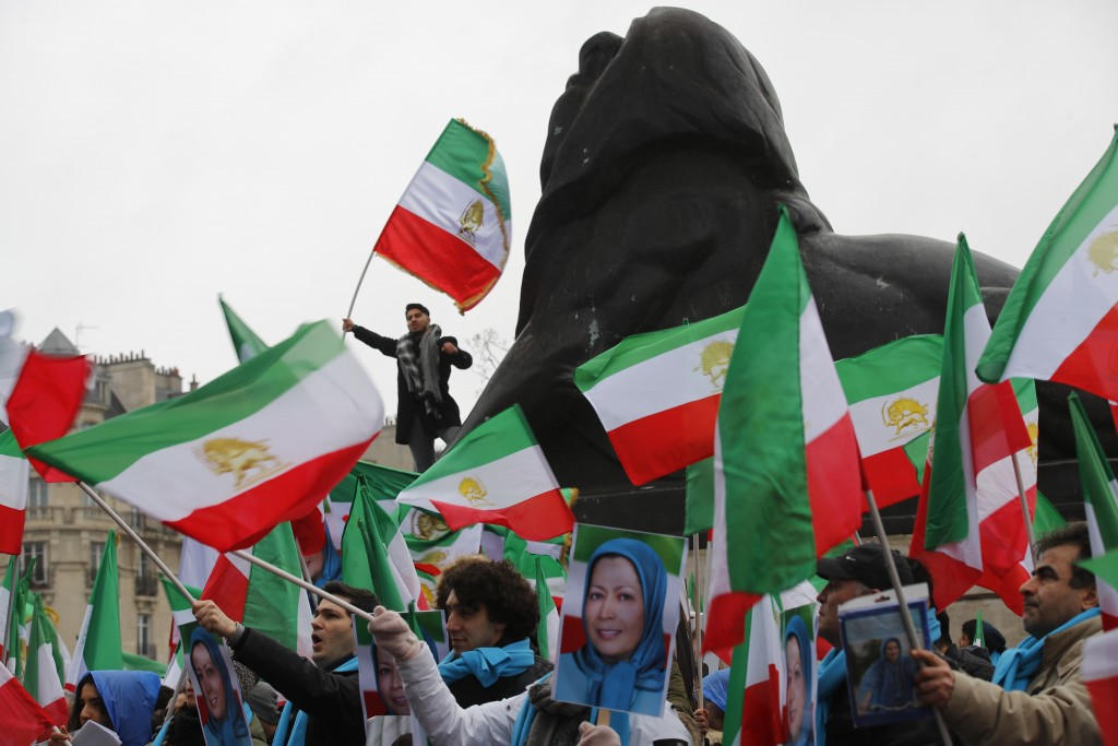 Demonstrators carry posters of Maryam Rajavi, the leader of the National Council of Resistance of Iran, and wave Iranian flags during a protest in Par