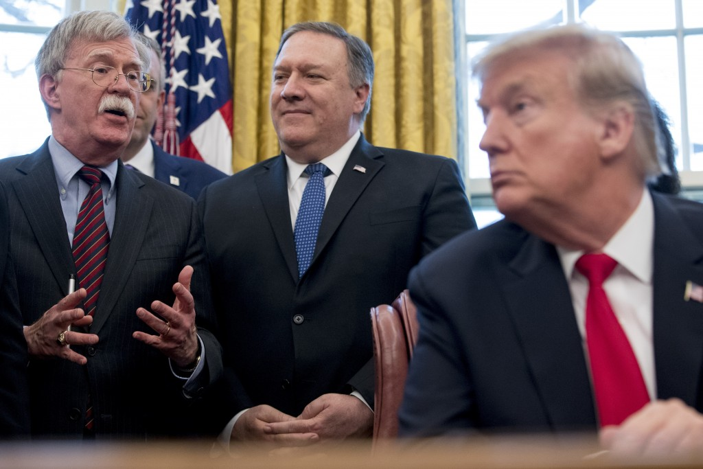From left, National Security Adviser John Bolton, accompanied by Secretary of State Mike Pompeo, and President Donald Trump, speaks before Trump signs