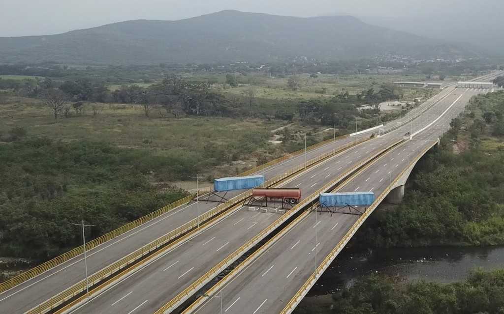 This Feb. 6, 2019 image taken from video, shows a fuel tanker, cargo trailers and makeshift fencing, blocking the Tienditas International Bridge in an