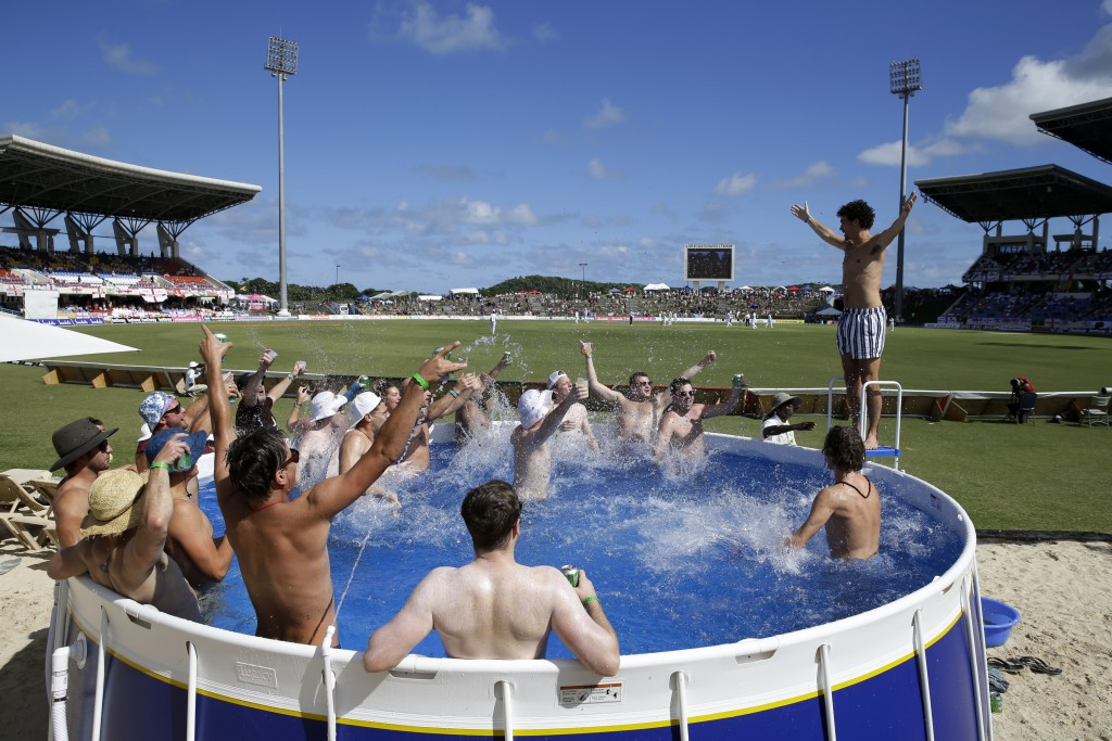 In this Jan. 31, 2019 photo, England cricket fans watch day one of the second Test cricket match against West Indies, from a pool at the Sir Vivian Ri...