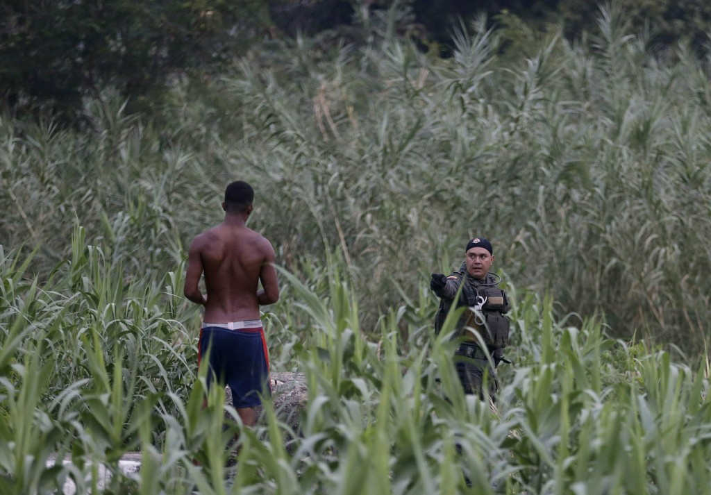 In this Feb. 5, 2019 photo, a Colombian police officer detains a smuggler who crossed the border illegally in La Parada, on the outskirts of Cucuta, C...
