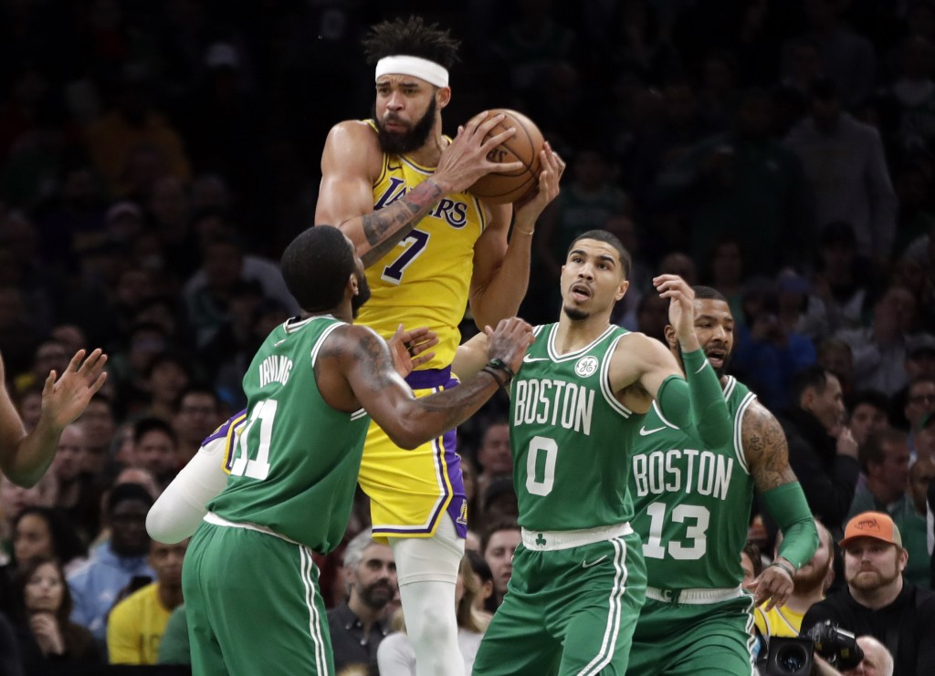Los Angeles Lakers center JaVale McGee (7) grabs a rebound against Boston Celtics guard Kyrie Irving (11), forward Jayson Tatum (0) and forward Marcus