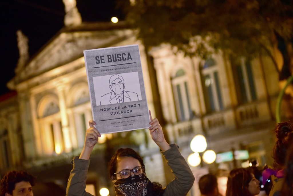 "A woman holds up a sign with a line drawing depicting Costa Rica's ex-President Oscar Arias and a message that reads in Spanish: ""WANTED: Oscar Arias"