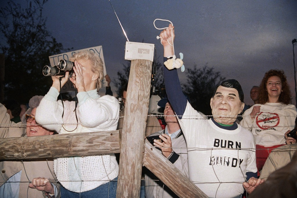 FILE - In this Jan. 25, 1989 file photo, a toy bunny is hung in effigy by Jerry Jackson of Atlanta Ga., wearing a Ronald Reagan mask, as a crowd celeb