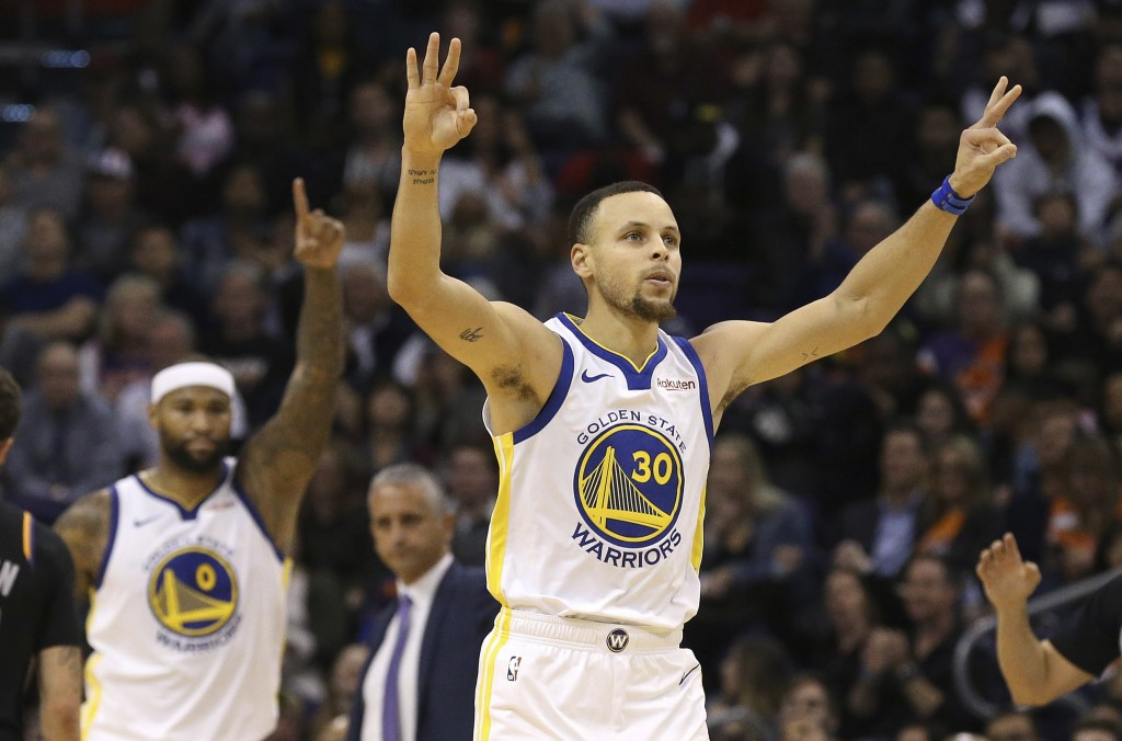 Golden State Warriors guard Stephen Curry (30) celebrates his 3-pointer against the Phoenix Suns along with Warriors center DeMarcus Cousins (0) durin
