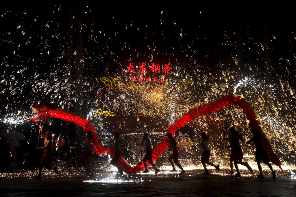 In this Saturday, Feb. 9, 2019, file photo, fire dragon dancers perform under a shower of sparks from molten iron during a temple fair at the Happy Va...
