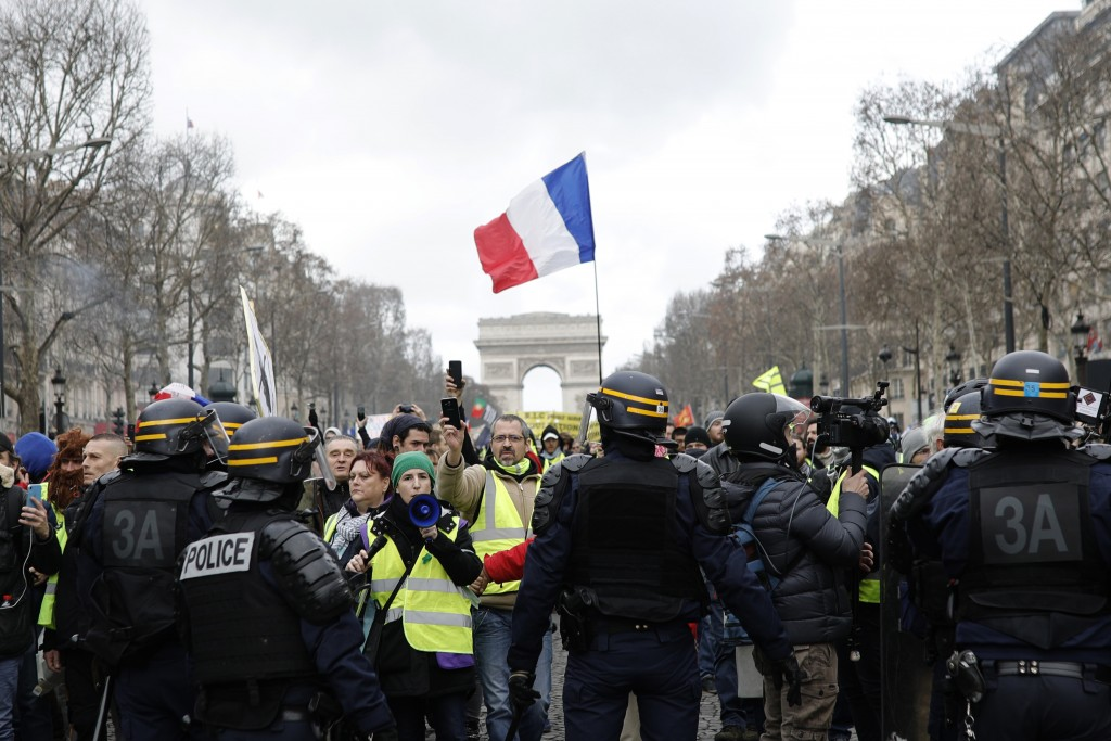 Yellow vest protesters walk down the famed Champs Elysees avenue to keep pressure on French President Emmanuel Macron's government, for the 13th strai...
