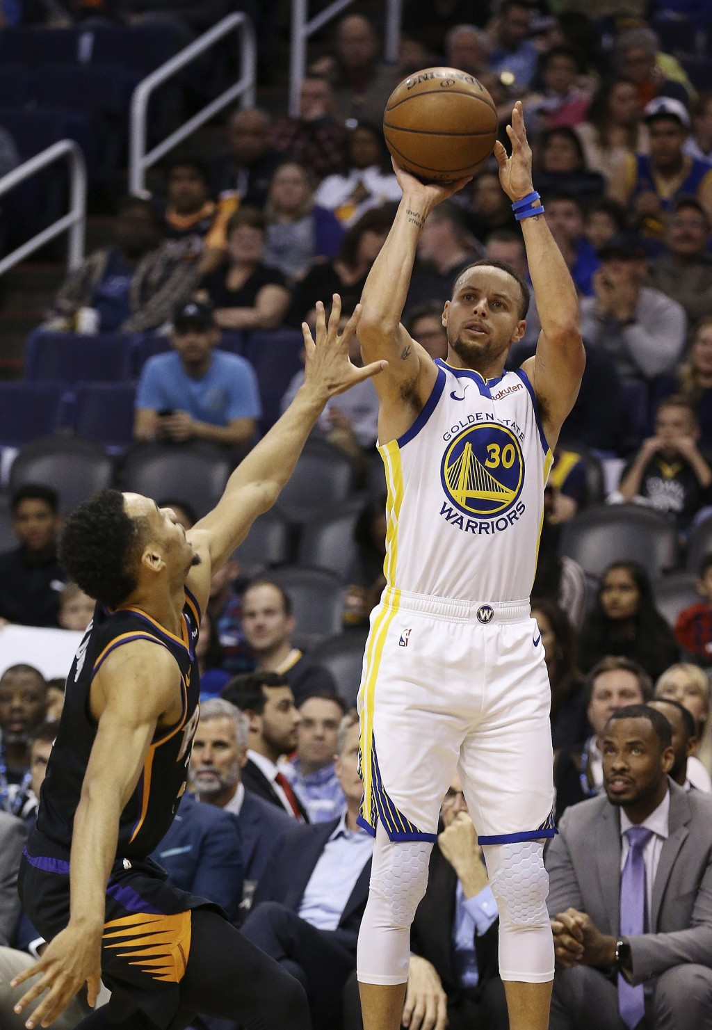 Golden State Warriors guard Stephen Curry (30) shoots over Phoenix Suns guard Elie Okobo during the first half of an NBA basketball game Friday, Feb.