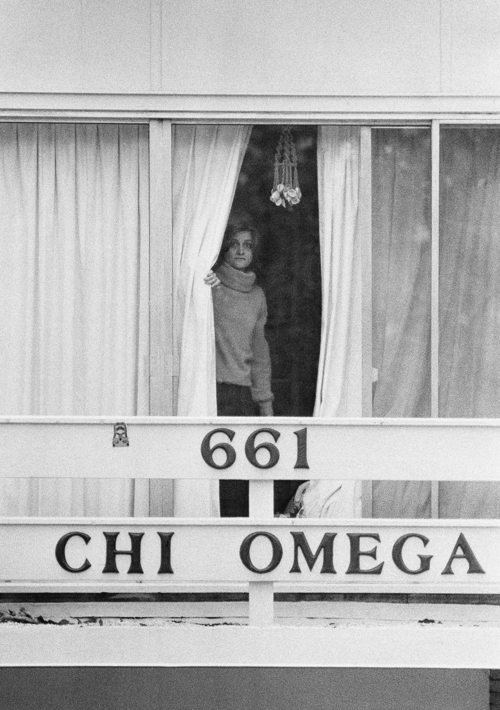 FILE - In this Jan. 15, 1978 file photo, an unidentified woman peers through drapes on the second story balcony of the Chi Omega sorority house at Flo