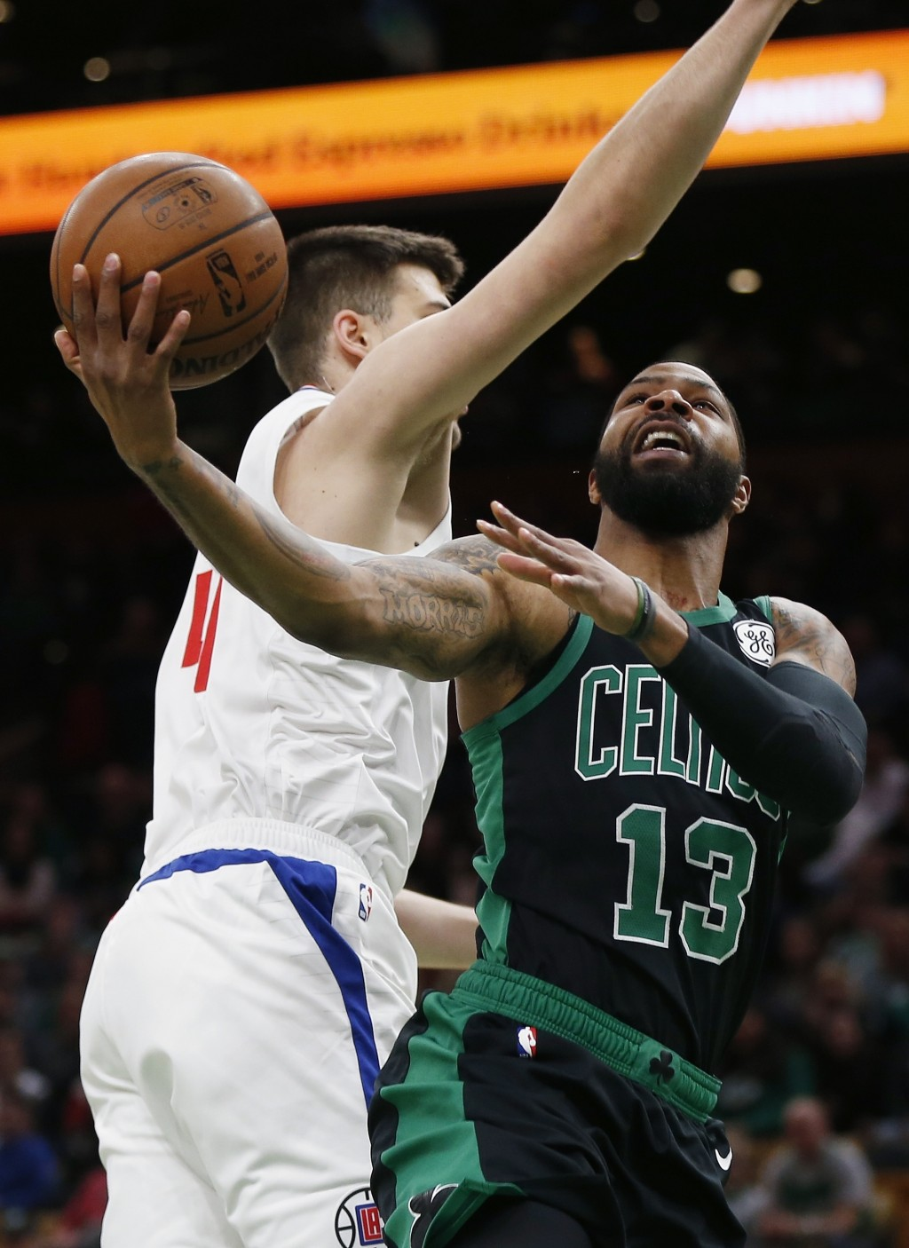 Boston Celtics' Marcus Morris (13) shoots against Los Angeles Clippers' Milos Teodosic (4) during the first half of an NBA basketball game in Boston,
