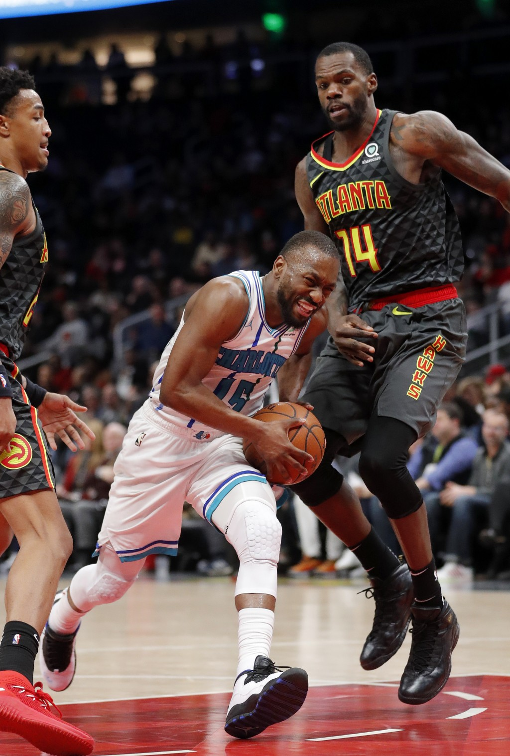 Charlotte Hornets guard Kemba Walker (15) drives against Atlanta Hawks center Dewayne Dedmon (14) during the second half of an NBA basketball Saturday