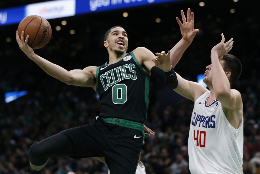 Boston Celtics' Jayson Tatum (0) shoots against Los Angeles Clippers' Ivica Zubac (40) during the first half of an NBA basketball game in Boston, Satu