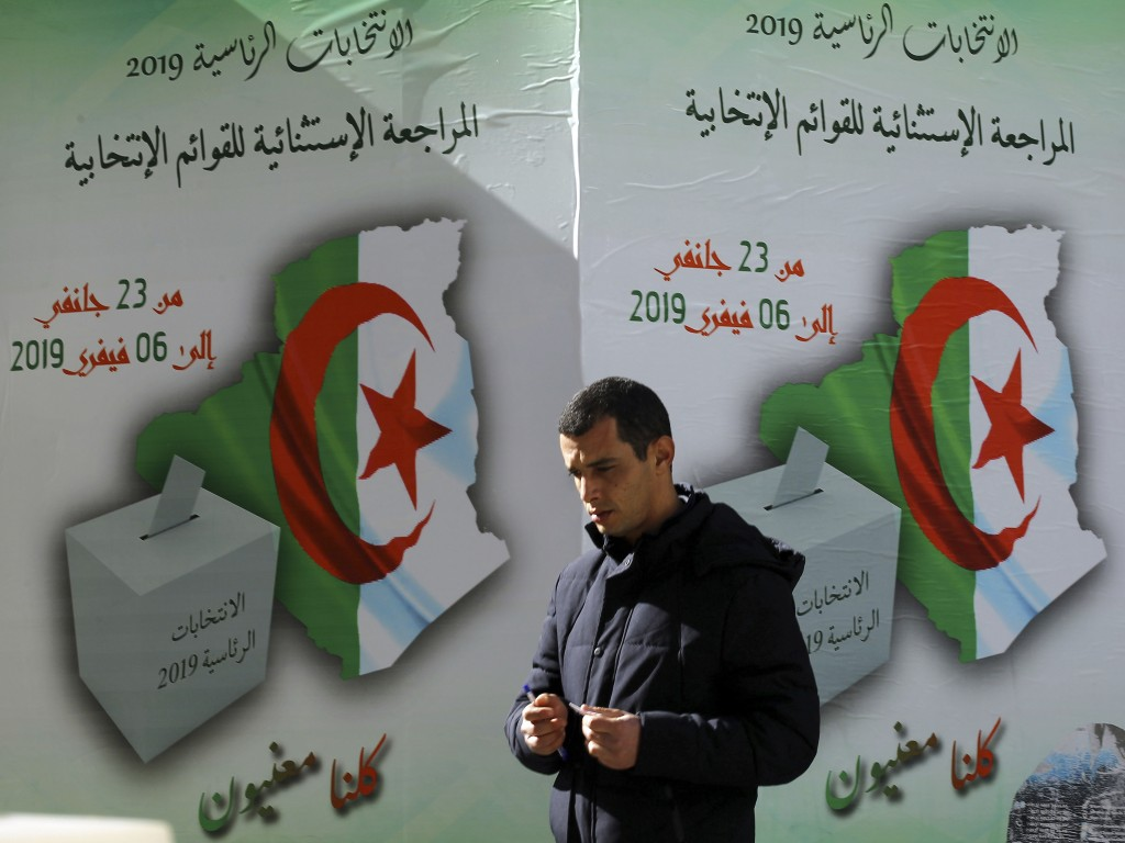 In this Feb. 5, 2019, photo, a man walks past a poster asking citizen to register to vote in Algiers. More than 180 people want to run for president o...