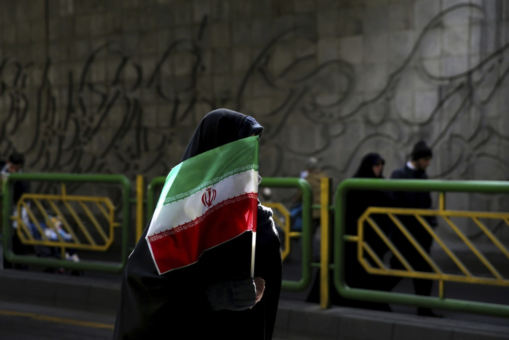 FILE - In this Feb. 11, 2016 file photograph, an Iranian woman holds the national flag during a rally commemorating the 37th anniversary of the Islami