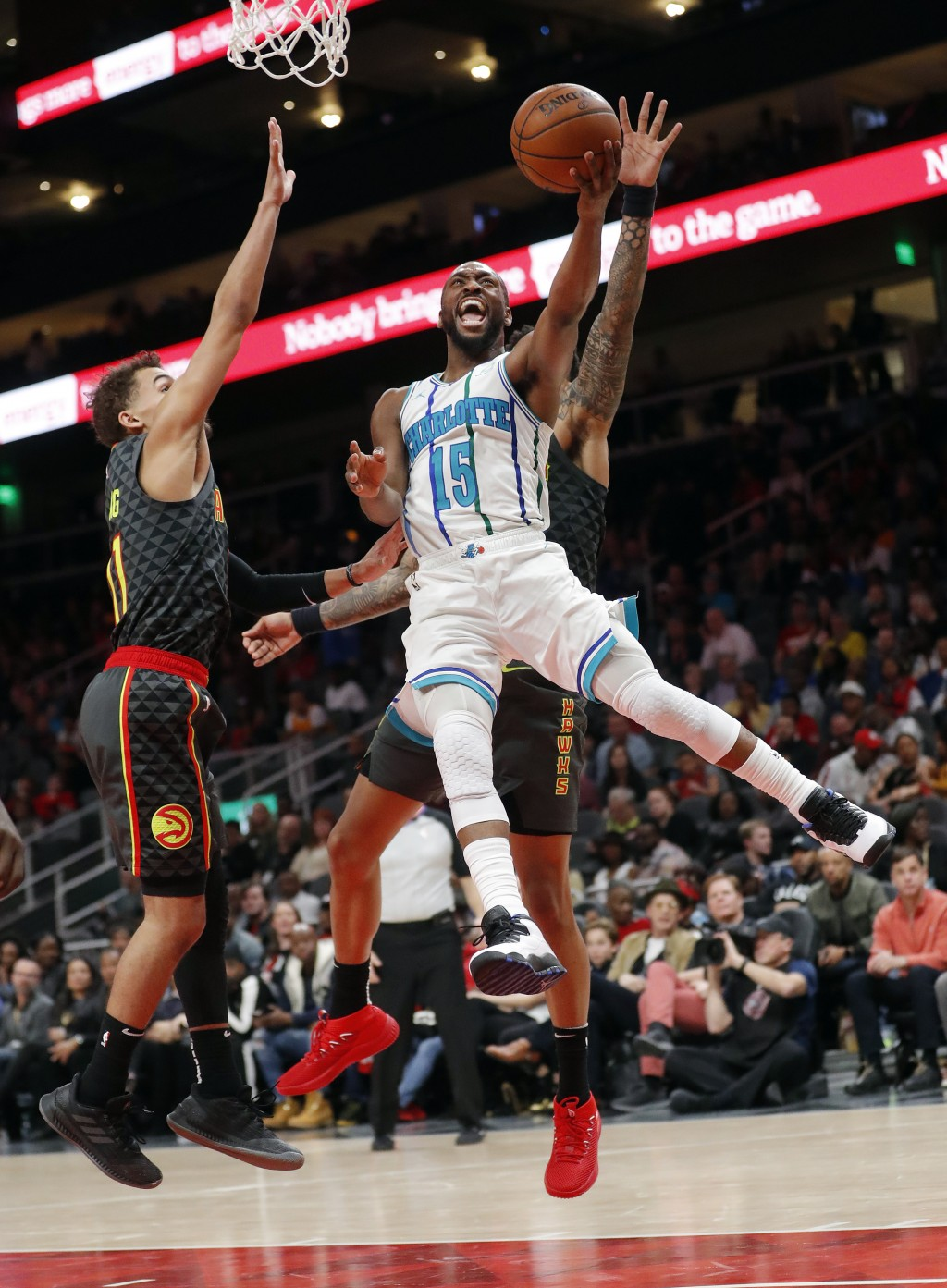 Charlotte Hornets guard Kemba Walker (15) scores as Atlanta Hawks guard Trae Young (11) defends during the second half of an NBA basketball Saturday,