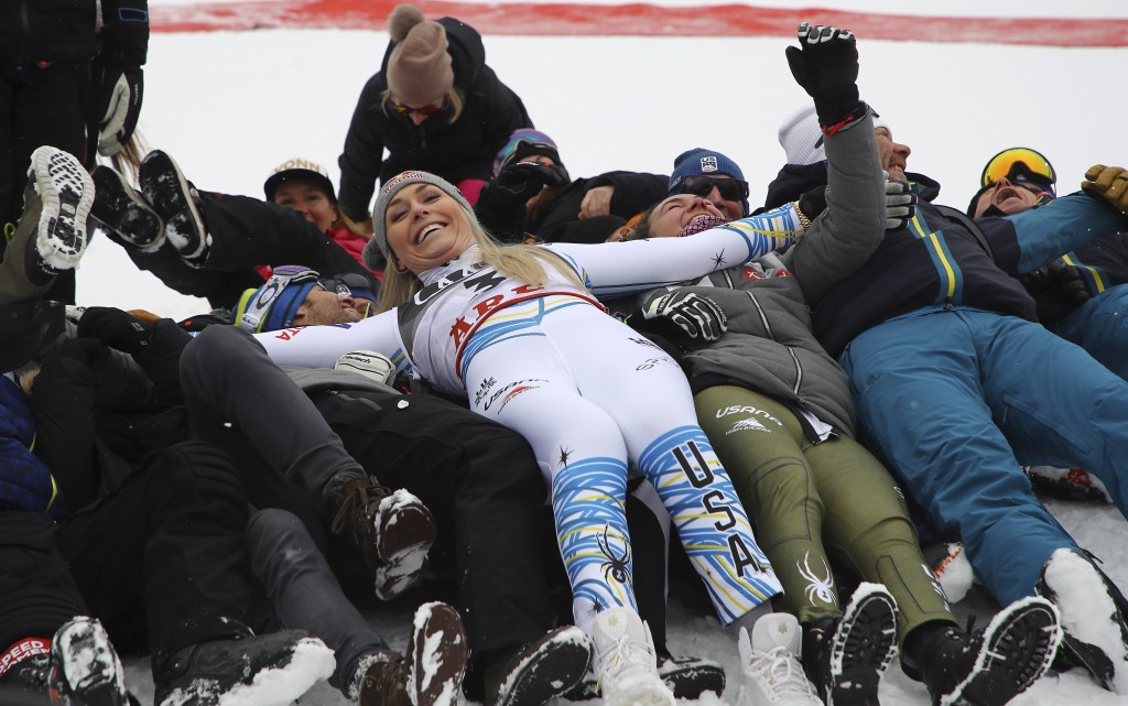 Third placed United States' Lindsey Vonn celebrates with her team in the finish area after the women's downhill race, at the alpine ski World Champion...