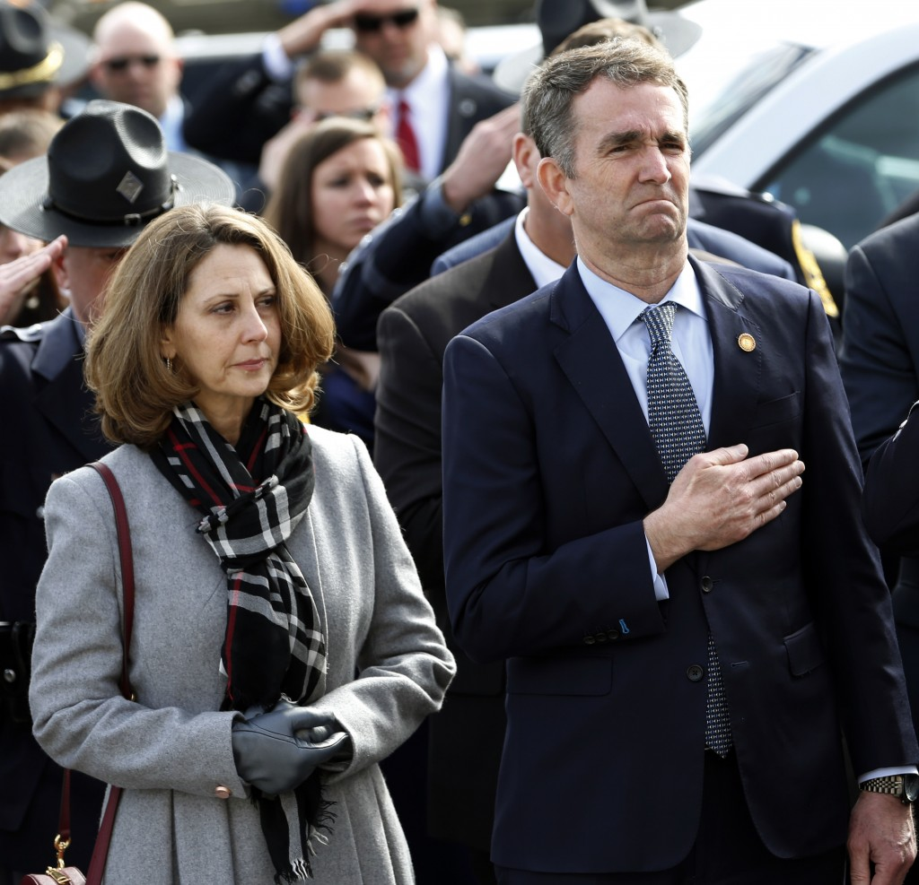 Virginia Gov. Ralph Northam, right, and his wife Pam, watch as the casket of fallen Virginia State Trooper Lucas B. Dowell is carried to a waiting tac...