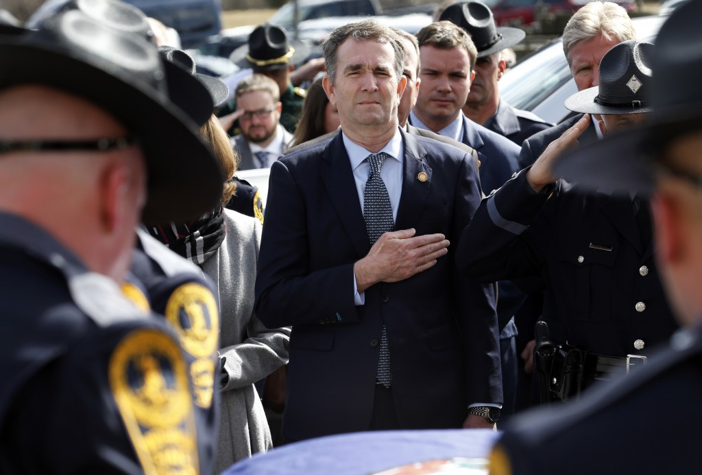 Virginia Gov. Ralph Northam, left, and his wife Pam, watch as the casket of fallen Virginia State Trooper Lucas B. Dowell is carried to a waiting tact...