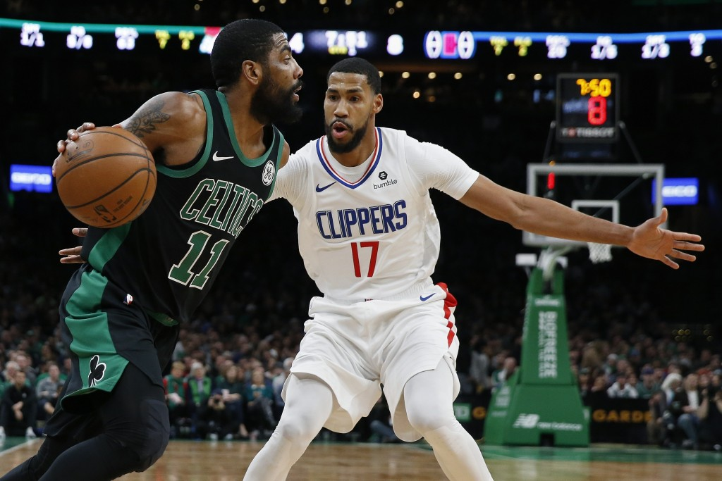 Boston Celtics' Kyrie Irving (11) drives past Los Angeles Clippers' Garrett Temple (17) during the first half of an NBA basketball game in Boston, Sat