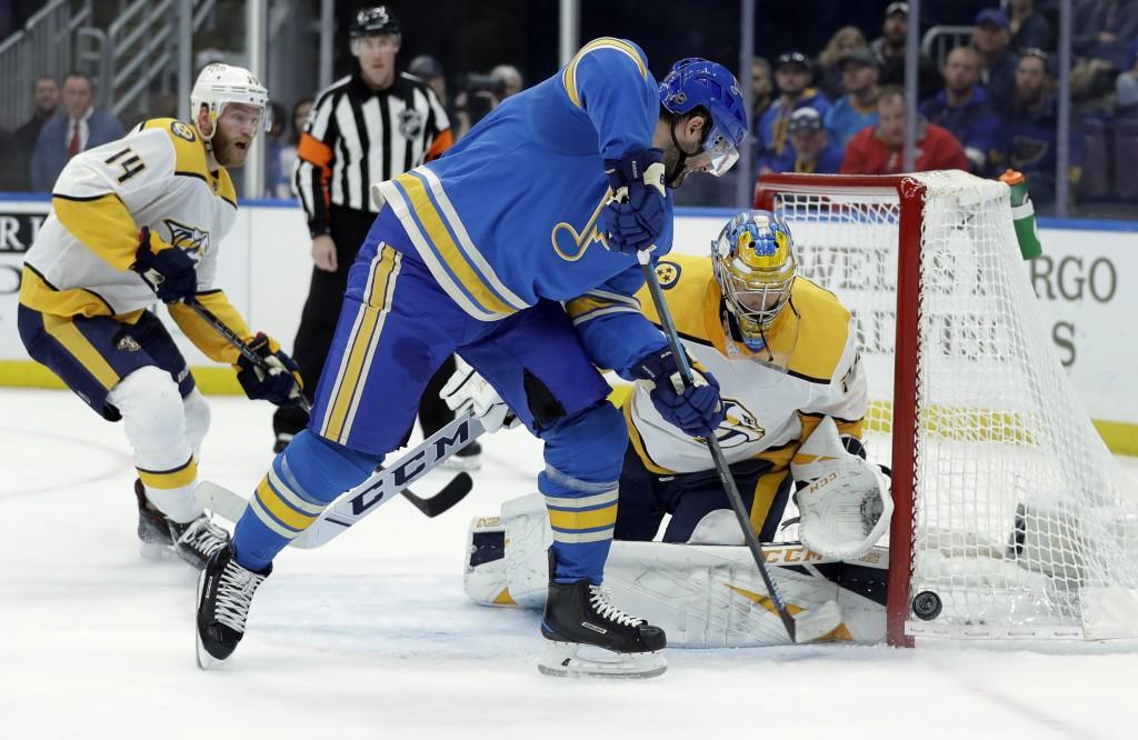 St. Louis Blues' Pat Maroon, center, is unable to score past Nashville Predators goaltender Pekka Rinne, of Finland, as Predators' Mattias Ekholm (14)