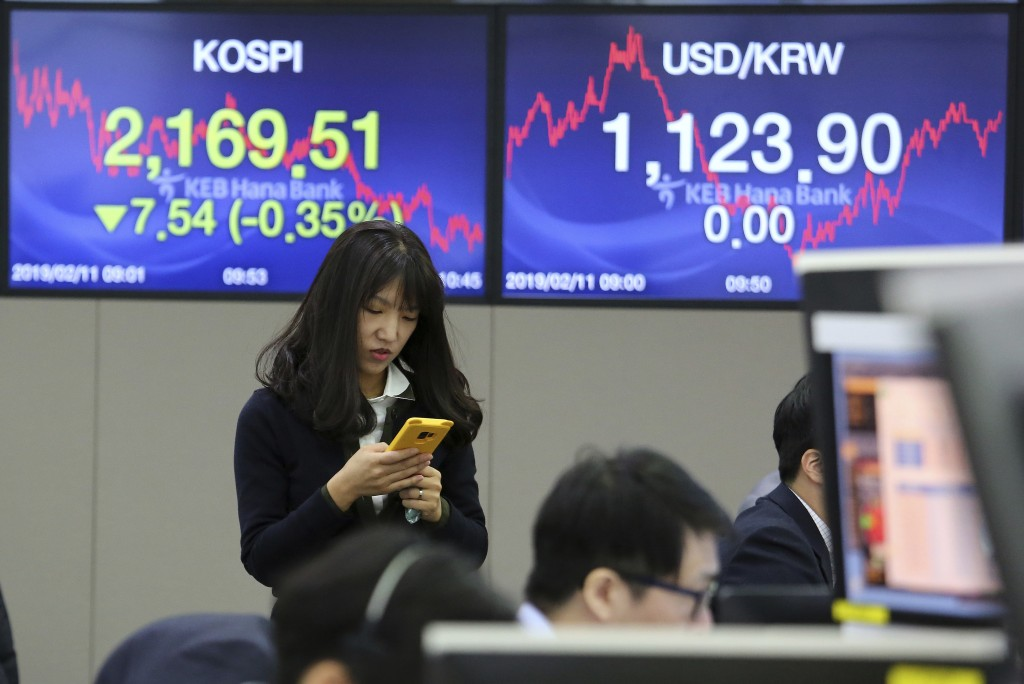 A currency trader watches her smartphone at the foreign exchange dealing room of the KEB Hana Bank headquarters in Seoul, South Korea, Monday, Feb. 11...