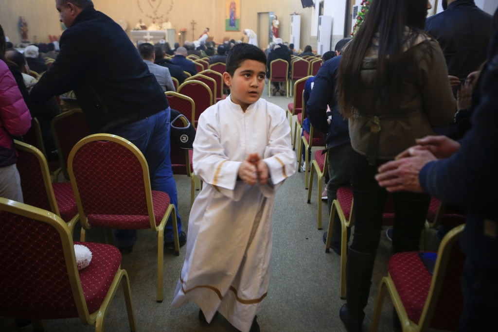 In this Jan. 20, 2019 photo, an altar boy shakes people's hands during Sunday service at Mart Shmony Orthodox Church in Irbil, Iraq. Two years after i...