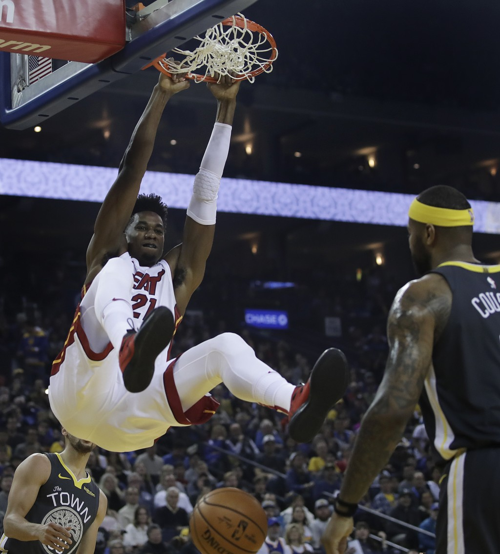 Miami Heat center Hassan Whiteside, left, scores in front of Golden State Warriors' DeMarcus Cousins during the first half of an NBA basketball game d...
